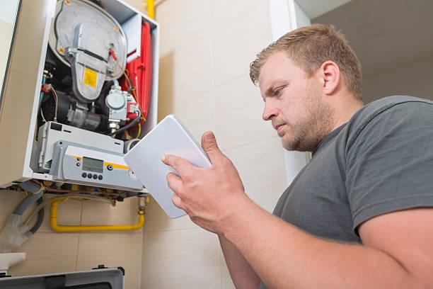 Técnico en reparación de Gas horno usando tableta digital - foto de stock