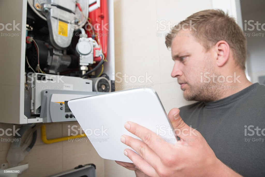 Technician repairing Gas Furnace using digital tablet stock photo