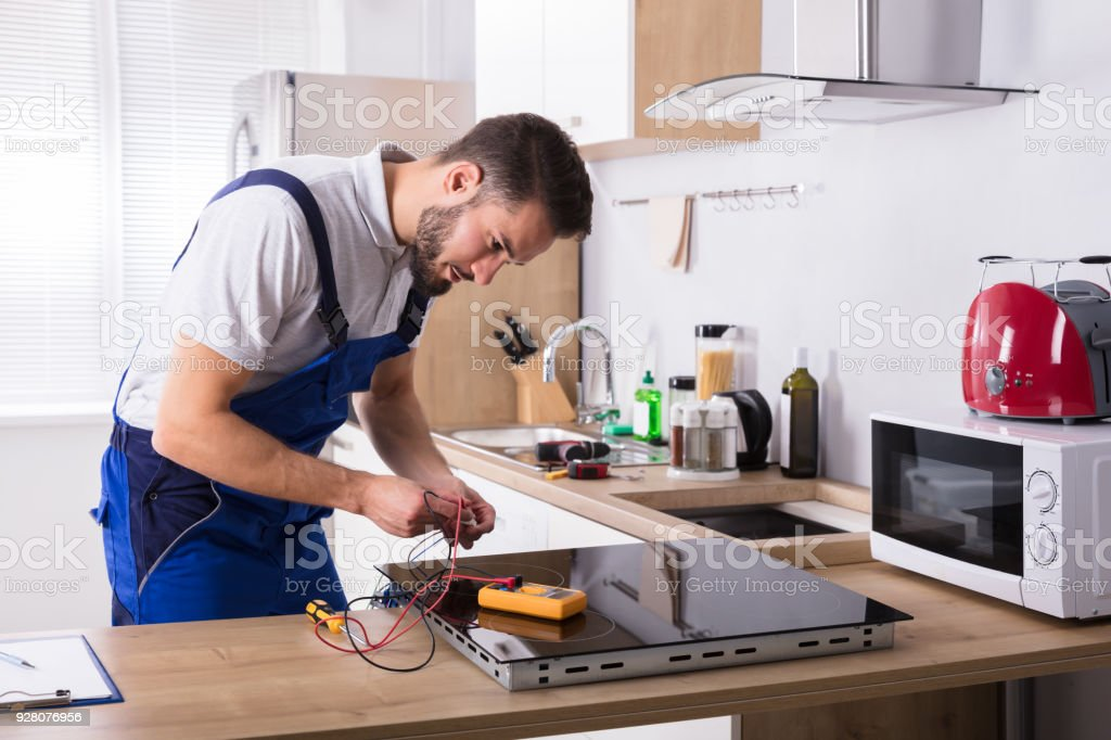 Technician Repairing Induction Stove In Kitchen stock photo