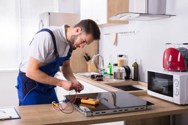 technicus reparatie inductie fornuis in de keuken - huishoudelijk apparaat stockfoto's en -beelden