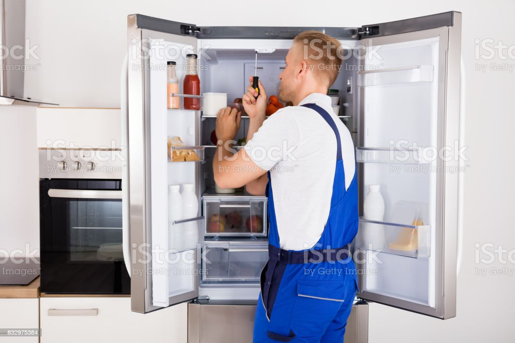 Technician Repairing Refrigerator stock photo