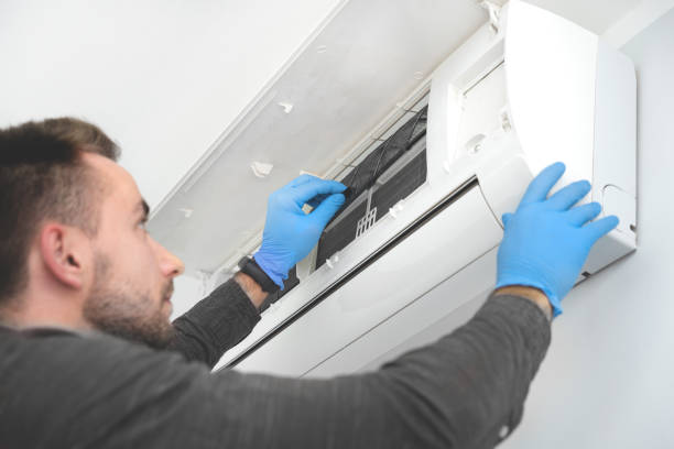Technician replacing filter in air conditioner stock photo