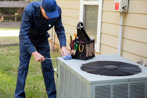 Senior Adult air conditioner Technician/Electrician  services outdoor unit.