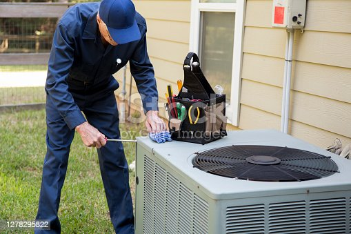 Senior Adult air conditioner Technician/Electrician  services outdoor unit.