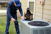 istock Technician services outside AC units and generator. 1278295822