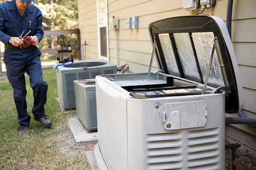 Senior Adult air conditioner Technician/Electrician  services outdoor AC unit and the Gas Generator.