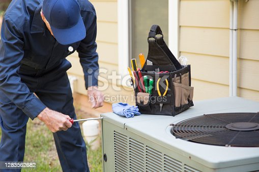 Senior Adult air conditioner Technician/Electrician  services outdoor AC unit and the Gas Generator.  He checks the oil in the generator.
