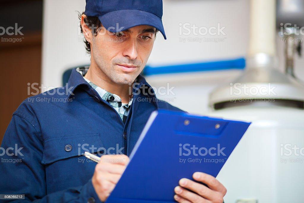 Technician servicing an hot-water heater stock photo