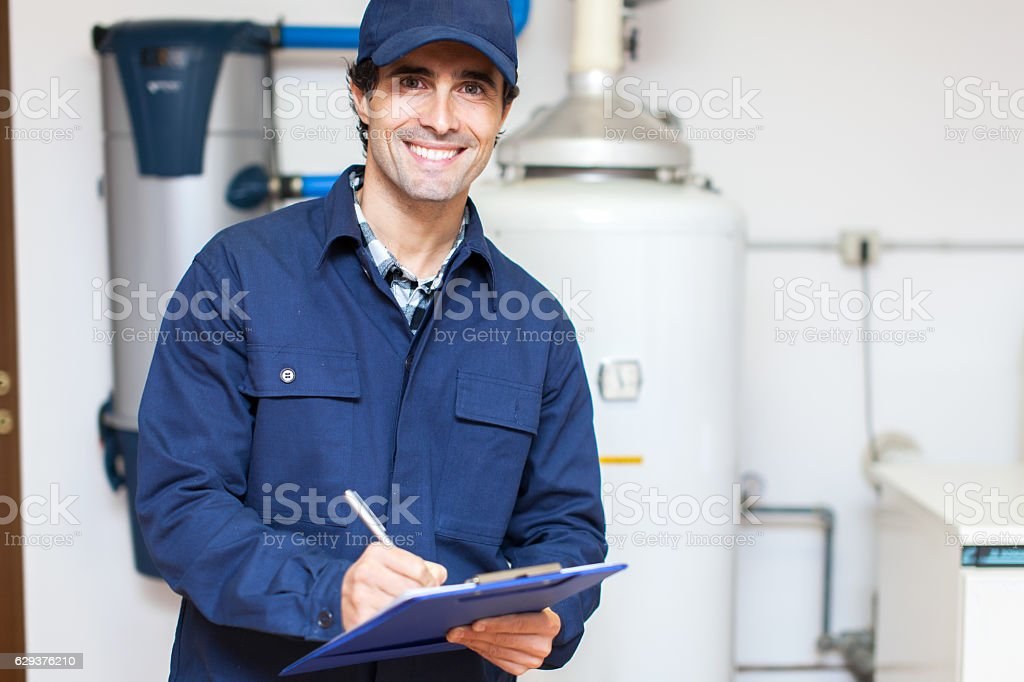Technician servicing an hot-water heater stock photo