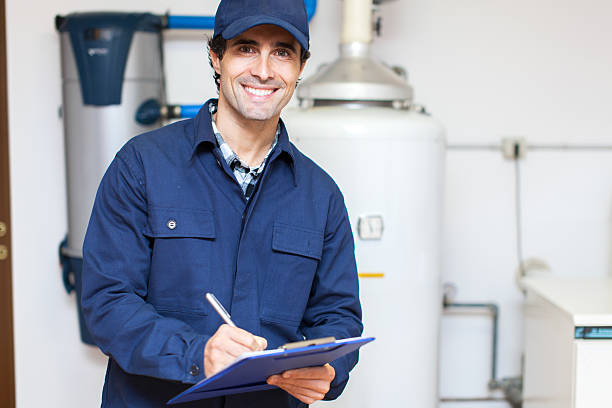 technician servicing an hot-water heater - plumber stock photos and pictures