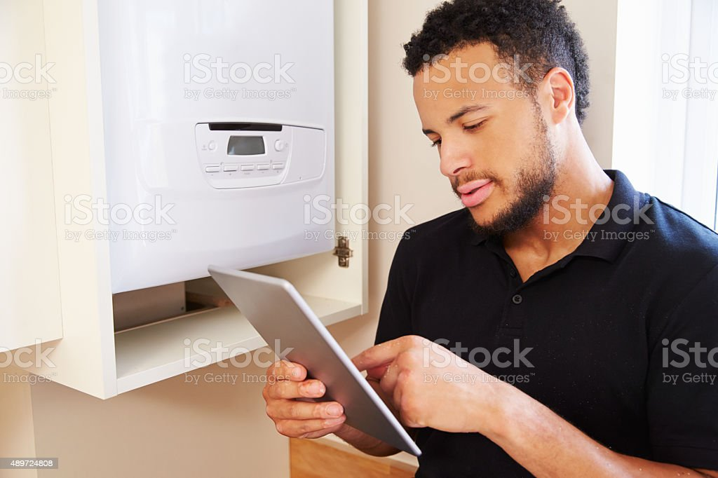 Technician servicing boiler using tablet computer stock photo