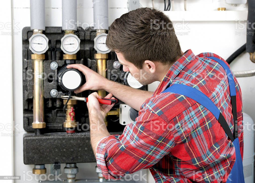 Technician servicing heating boiler stock photo