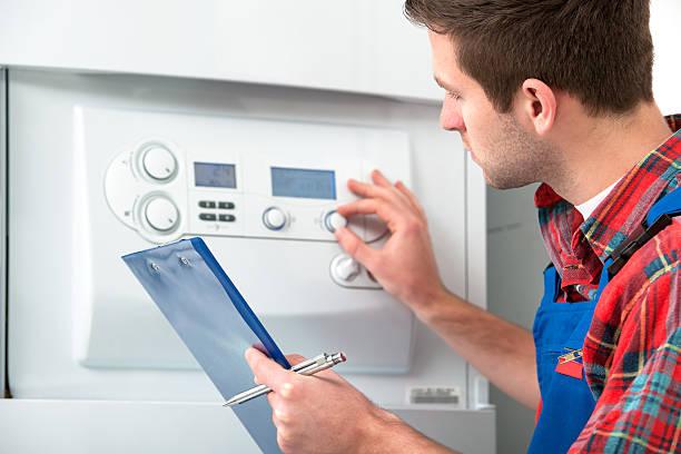 Technician servicing heating boiler stock photo