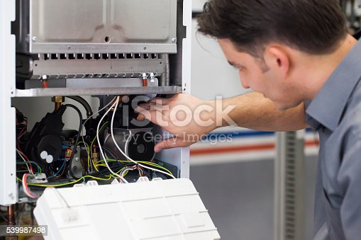 istock Technician servicing heating boiler 539987498