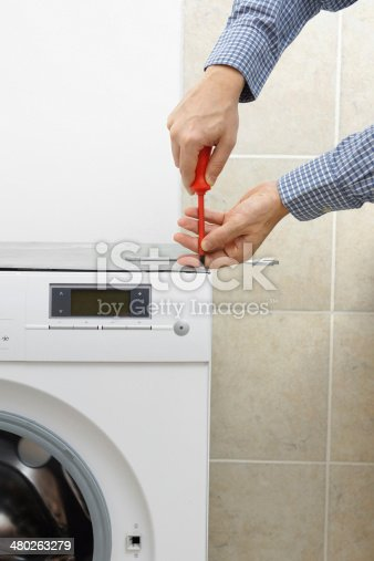 487597124 istock photo Technician servicing washing machine using screwdriver 480263279
