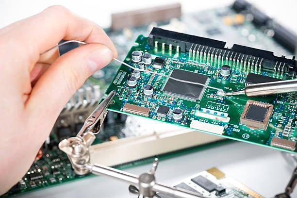 Technician soldering elements Electronic technician holding tin wire and soldering elements on circuit board.  soldering iron stock pictures, royalty-free photos & images