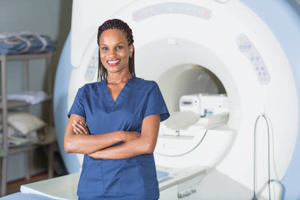 Technician standing in front of MRI scanner stock photo