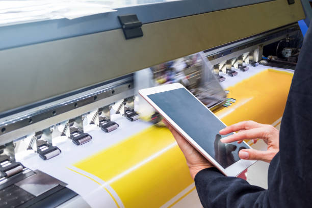Technician touch control tablet on format inkjet printer during yellow vinyl stock photo