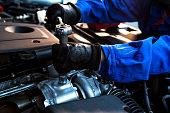 istock Technician uses hands of car mechanic in auto repairing service. 1216308824