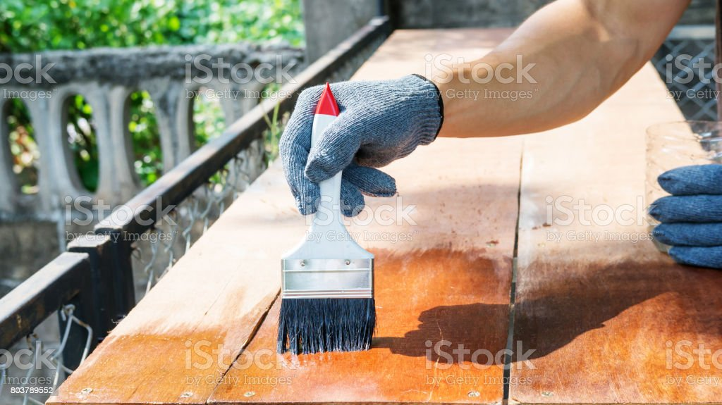 technician using a varnish paint with a wooden table. stock photo
