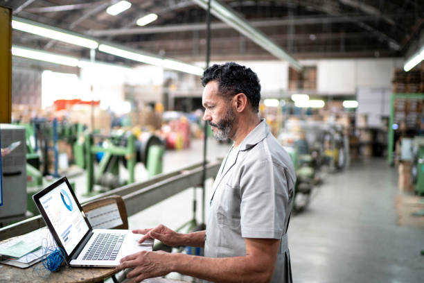 Technician using laptop while working in a factory Technician using laptop while working in a factory manufacturing stock pictures, royalty-free photos & images