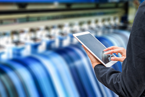 istock Technician using tablet control with format large inkjet printing blue vinyl 931155882