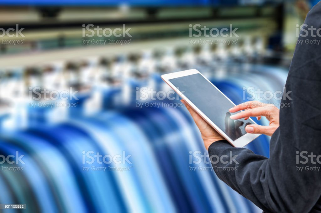 Technician using tablet control with format large inkjet printing blue vinyl stock photo