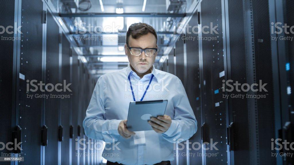 IT-Techniker geht durch die Reihen der Server-Racks im Rechenzentrum. Gleichzeitig arbeitet er an einem Tablet-Computer. – Foto