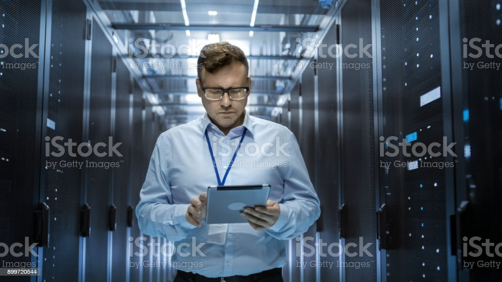 IT Technician Walks Through Rows of Server Racks in Data Center. Simultaneously He Works on a Tablet Computer. stock photo