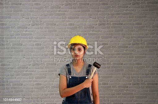 istock Technician woman ware yellow helmet with grey T-shirt and denim jeans apron dress standing and steel hammer in hand. 1014544502