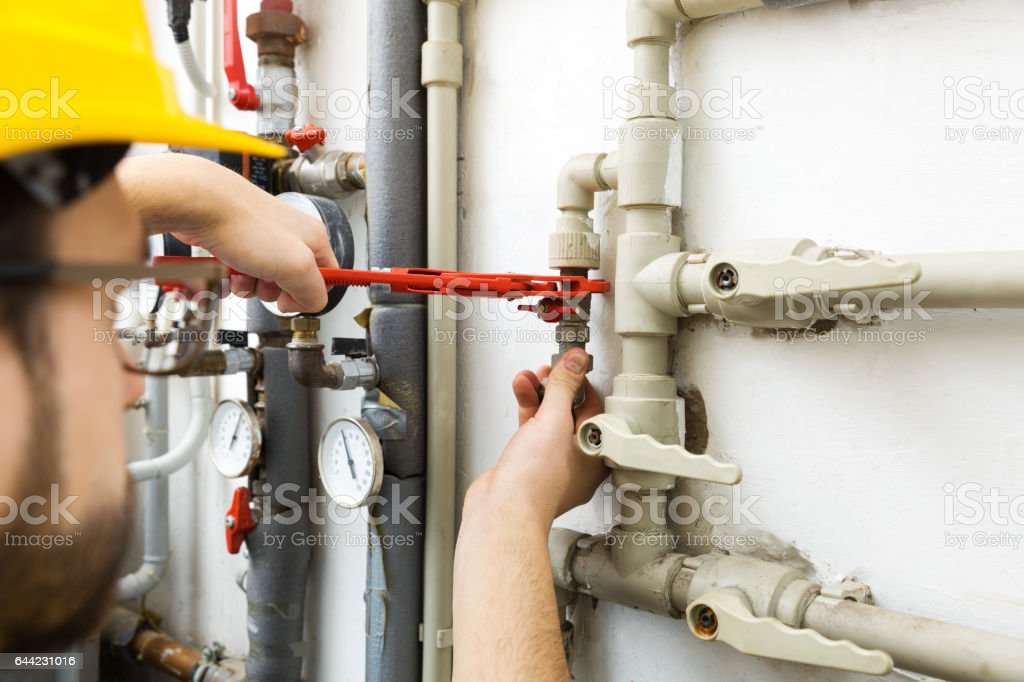 technician worker doing maintenance jobs for house heating system stock photo