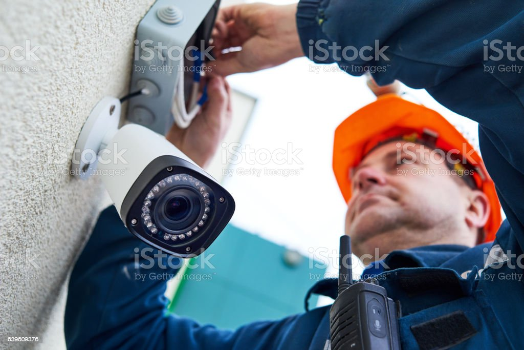 Technician worker installing video surveillance camera on wall​​​ foto