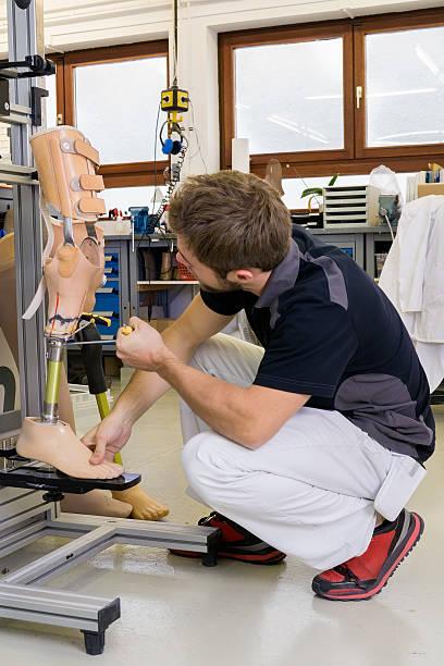 technician working on prosthetic leg parts. - membre photos et images de collection