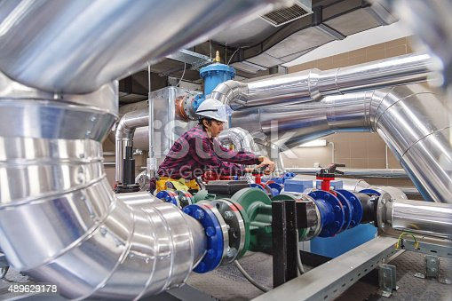 In utility or factory one technician or engineers working on a valve on building technical equipment or industrial site