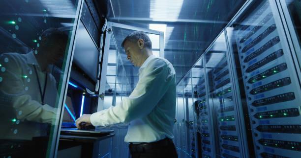technicus werkt op een laptop in een datacenter - datacenter stockfoto's en -beelden