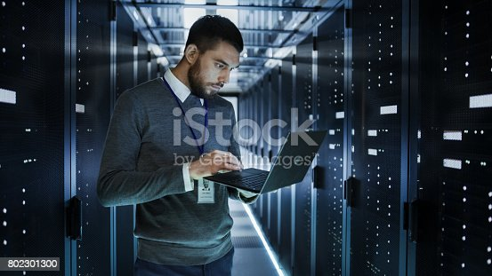 802303672istockphoto IT Technician Works on a Laptop in Big Data Center full of Rack Servers. He Runs Diagnostics and Maintenance, Sets up System. 802301300