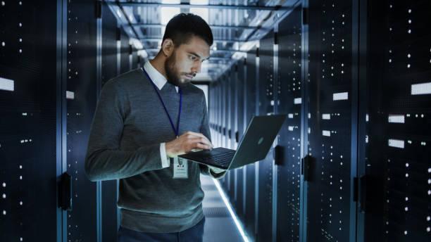 it 技術者は大きなデータ センター ラック マウント型サーバの完全にラップトップ上で動作します。彼の実行の診断とメンテナンス、システムを設定します。 - エンジニア ストックフォトと画像