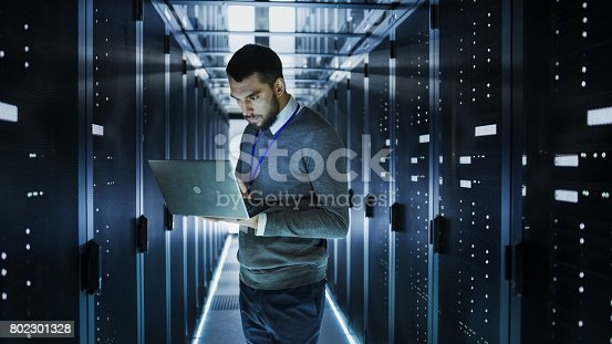 802303638istockphoto IT Technician Works on a Laptop in Big Data Center full of Rack Servers. He Runs Diagnostics and Maintenance, Sets up System. 802301328