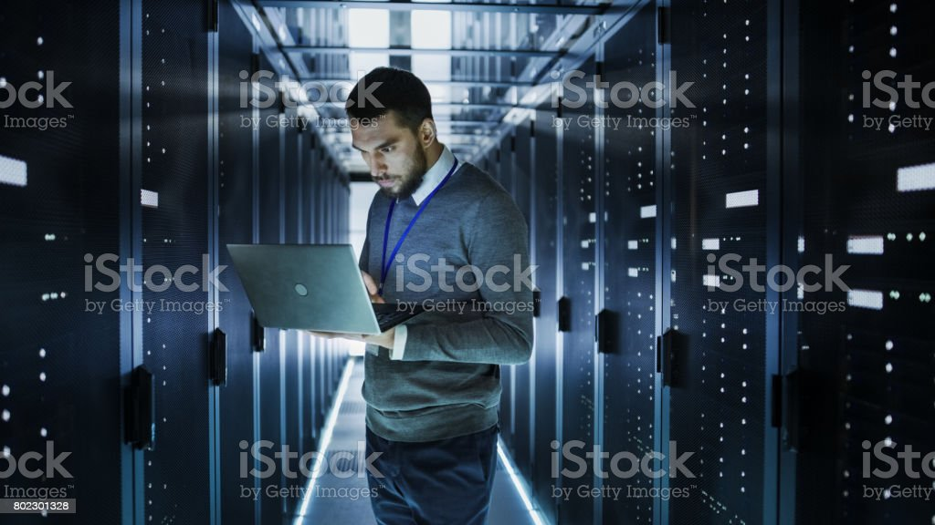 IT Technician Works on a Laptop in Big Data Center full of Rack Servers. He Runs Diagnostics and Maintenance, Sets up System. stock photo