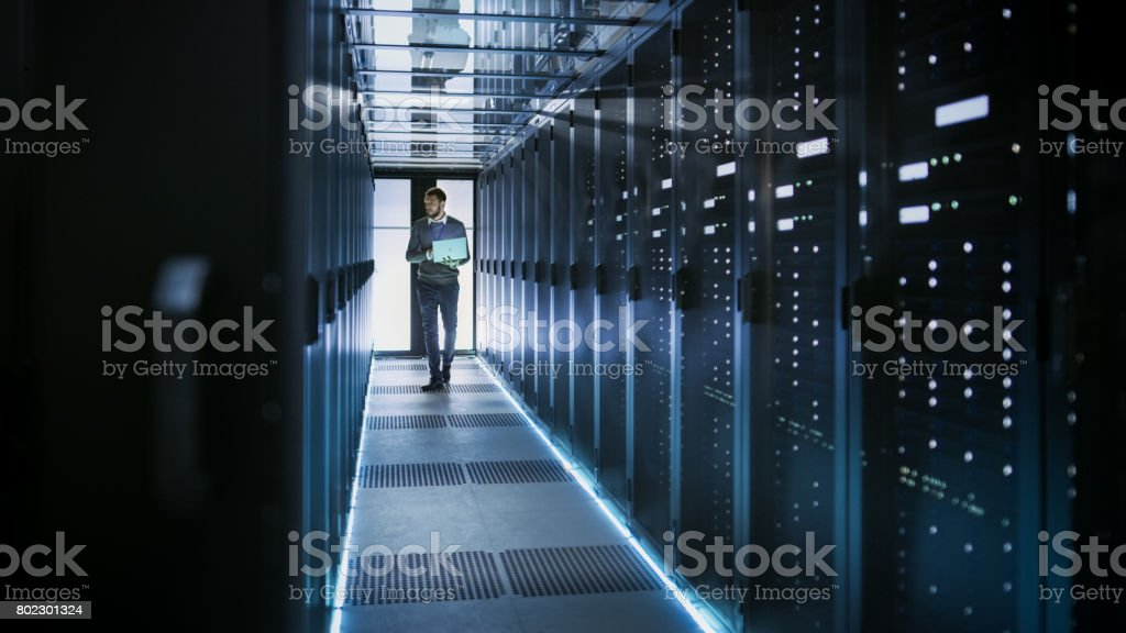 IT Technician Works on Laptop in Big Data Center full of Rack Servers. He Runs Diagnostics and Maintenance, Sets System Up. stock photo