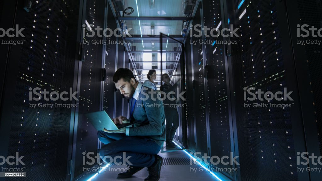 IT Technician Works on Laptop in Big Data Center full of Rack Servers. Multiple People Works at Data Center at the same time. royalty-free stock photo
