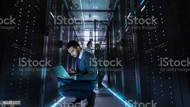 It Technician Works On Laptop In Big Data Center Full Of Rack Servers Multiple People Works At Data Center At The Same Time Stock Photo - Download Image Now