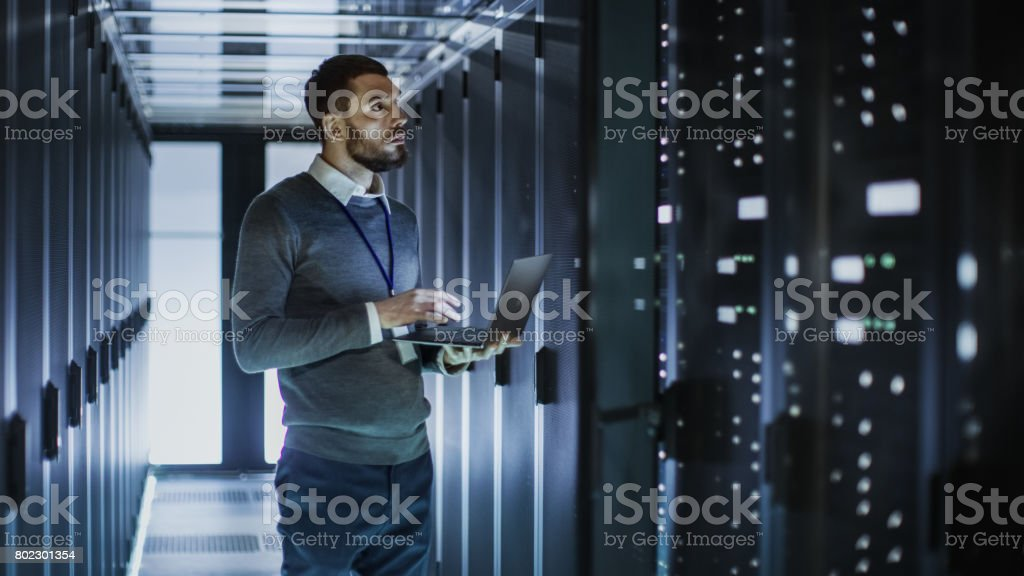 IT Technician Works on Laptop next to a Server Cabinet in Big Data Center. He Runs Diagnostics and Maintenance, Sets System Up. stock photo