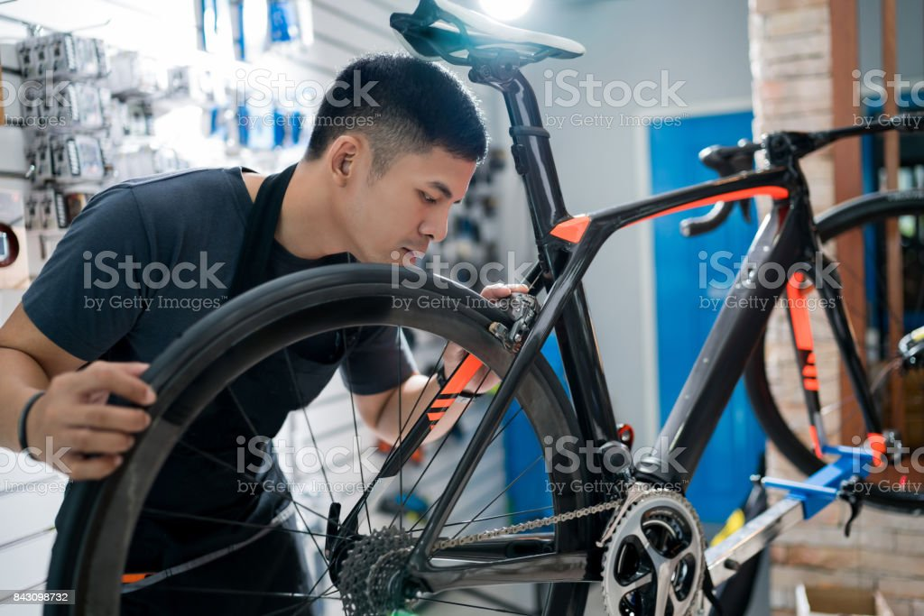 Technicians are repairing bicycles at shop sells stock photo