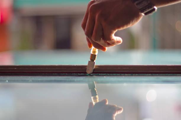 techniker sind schneiden werkzeuge geschliffenes glas nach kundengröße verwenden. - fensterbauer stock-fotos und bilder