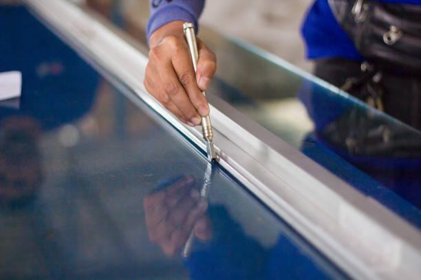 techniker sind schneidwerkzeuge, geschliffenes glas nach kundengröße verwenden - fensterbauer stock-fotos und bilder