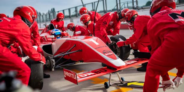 Techniker, die Reifen zu wechseln, während Formel Boxenstopp – Foto