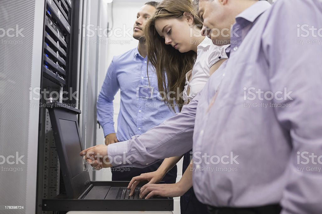 Technicians checking servers with laptop stock photo