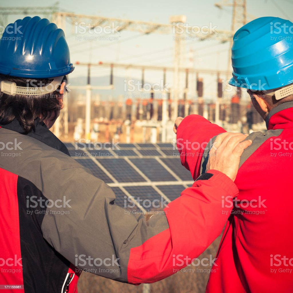 Technicians engineer working at photovoltaic farm royalty-free stock photo