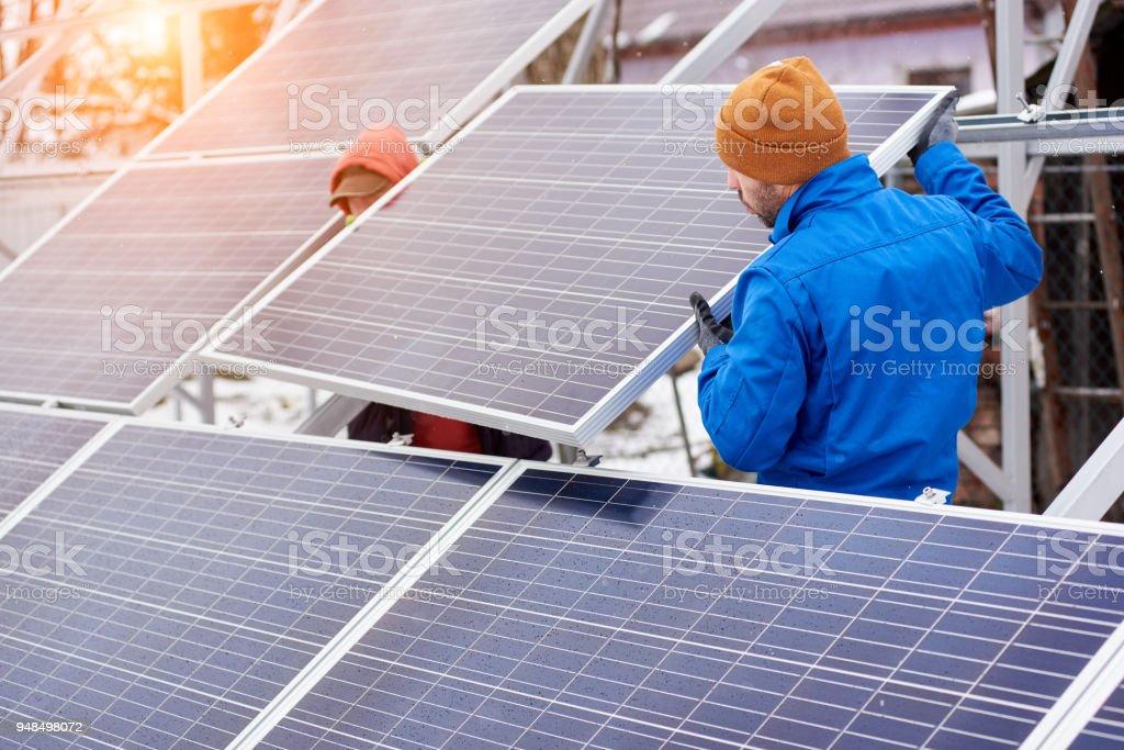 Técnicos en trajes azul montaje paneles solares fotovoltaicos en el techo de la casa moderna. - Foto de stock de Adulto libre de derechos